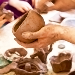 Hands holding pottery